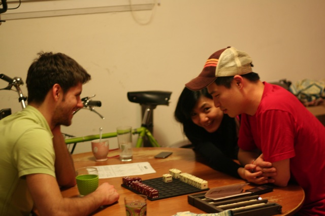 L, Carmen and Sam playing boardgames after dinner.