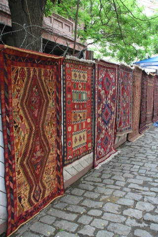 Carpets for sale on a wall next to a (very narrow) street in the old city.