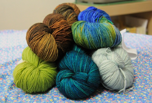 Clockwise from top left: Dragonfly yarns Dragon Sock in Mushroom Hunting B-Side and Djinni Sock in Admiral Benbow; Tosh Sock in Celadon and Cousteau; and Malabrigo Sock in Lettuce.