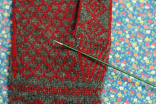 You can just see the ned red rungs through the gap. On the needle, the bottom stitch is the one that was left at the the bottom of the gap, and the top stitch is a new rung picked up through the gap. From here to the top, it's just like laddering up a dropped stitch.