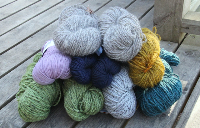 The full haul, l-r, top to bottom:  Two skeins undyed yarn from Marilyn; Swan's Island  Organic Fingering weight in Vintage Lilac, two skeinds Swan's Island Washable DK in Midnight (for a new hat for L), yellow/gold skein from Marilyn; Four skeins Fleece Artist Wool Tweed